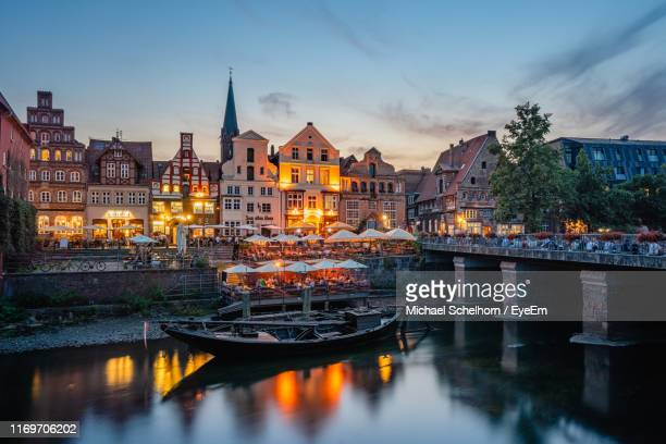 illuminated bridge over river amidst buildings against sky at dusk - lüneburg stock photos and pictures
