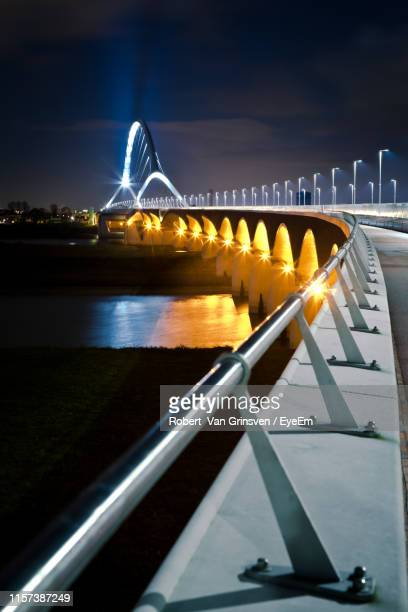 illuminated bridge over river at night - nijmegen stock pictures, royalty-free photos & images