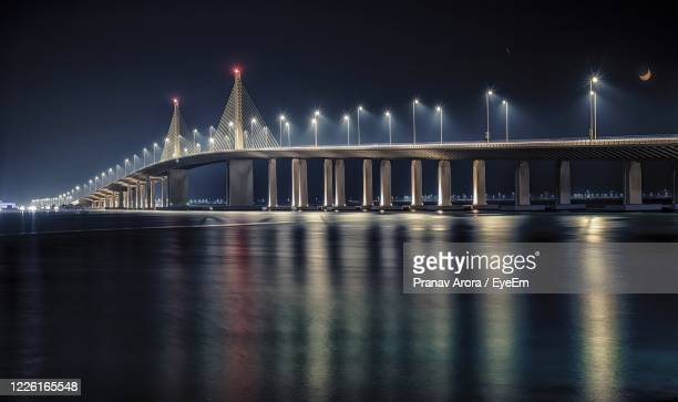illuminated bridge over river at night - abu dhabi stock pictures, royalty-free photos & images