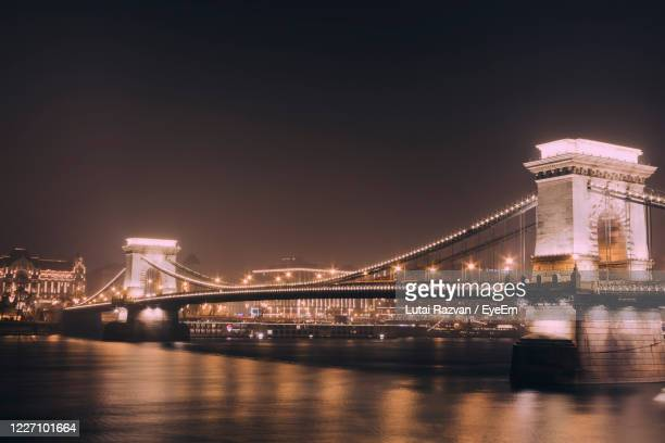 illuminated bridge over river at night - lutai razvan stock pictures, royalty-free photos & images