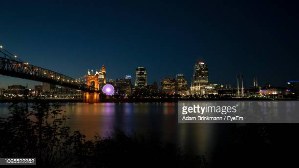 illuminated bridge over river by buildings against sky at night - cincinnati stock pictures, royalty-free photos & images