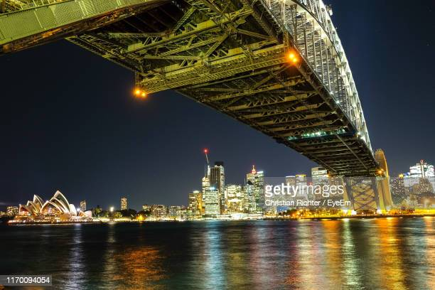 "illuminated bridge over river by buildings against sky at night - ""christian richter"" stock pictures, royalty-free photos & images"