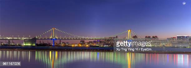illuminated bridge over river by buildings against sky at night - 全景 ストックフォトと画像