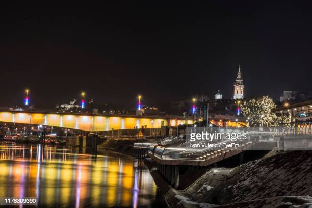 illuminated bridge over river by buildings in city at night - belgrade serbia stock pictures, royalty-free photos & images