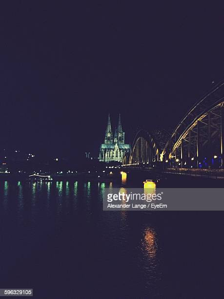 Illuminated Bridge Over River By Cologne Cathedral At Night