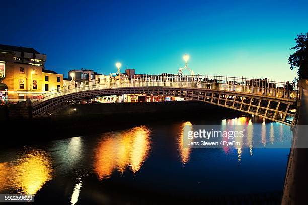 Illuminated Bridge Over River In City Against Clear Sky