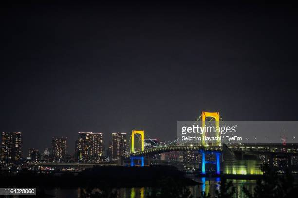 illuminated bridge over river in city against sky at night - seiichiro hayashi ストックフォトと画像