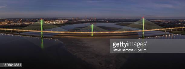 illuminated bridge over river in city against sky - widnes stock pictures, royalty-free photos & images