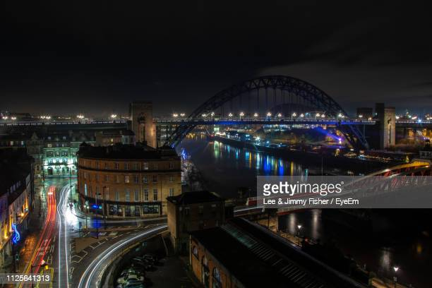 illuminated bridge over river in city at night - {{relatedsearchurl('london eye')}} stock photos and pictures