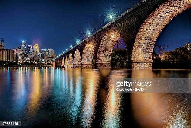 illuminated bridge over river in city at night - minneapolis stock photos and pictures