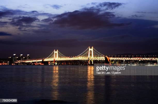 Illuminated Bridge Over River With City In Background At Night