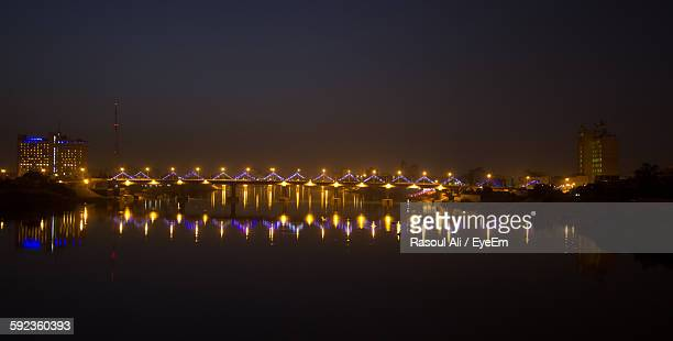 illuminated bridge over river with reflection against sky - baghdad stock pictures, royalty-free photos & images