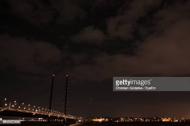 Illuminated Bridge Over Sea Against Sky At Night