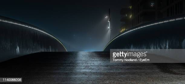 illuminated bridge over street against sky at night - oslo stock pictures, royalty-free photos & images