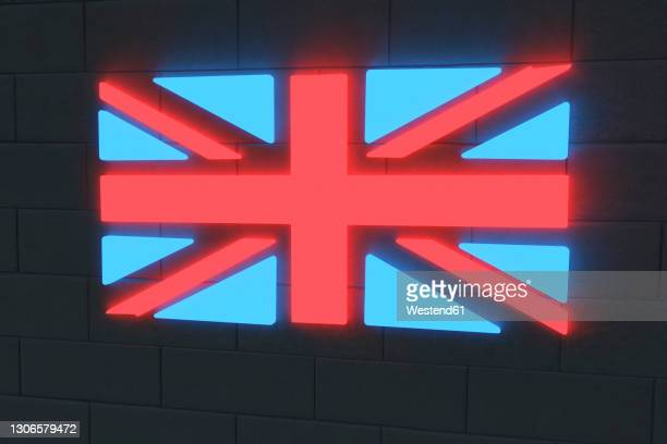 illuminated british flag on black brick wall - insignia stock pictures, royalty-free photos & images