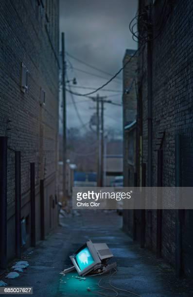 Illuminated broken monitor in city alley