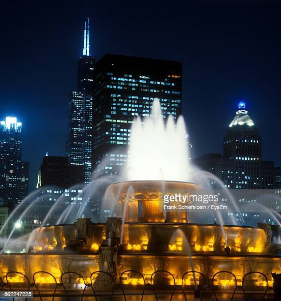 illuminated buckingham fountain in front of cityscape at night - millenium park stock photos and pictures