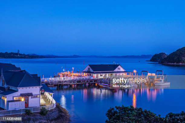 illuminated building on water at dawn - northland new zealand stock pictures, royalty-free photos & images