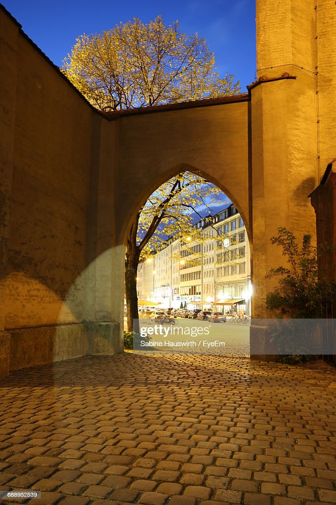 Illuminated Building Seen Through Archway In City At Night : Stock-Foto