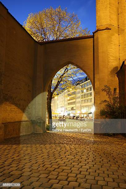 Illuminated Building Seen Through Archway In City At Night