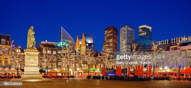 illuminated buildings against blue sky at night - the hague stock photos and pictures