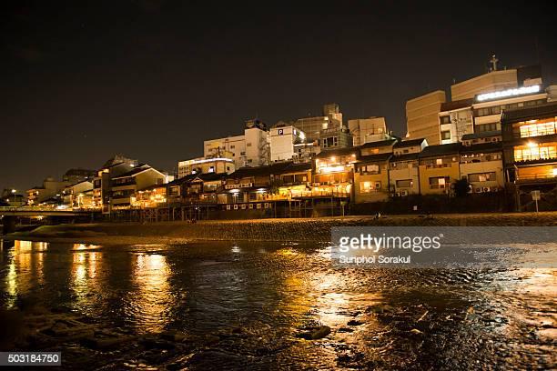 Illuminated buildings along Kamogawa River in the evening