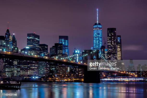 illuminated buildings and brooklyn bridge against sky at night - manhattan new york city stock pictures, royalty-free photos & images