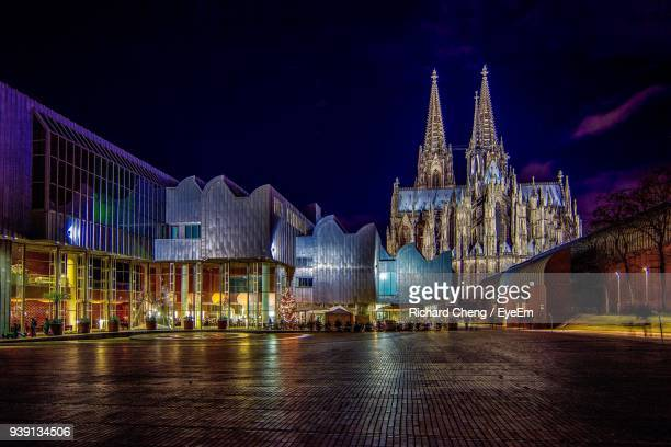 illuminated buildings and cologne cathedral against sky at night - cologne cathedral stock photos and pictures