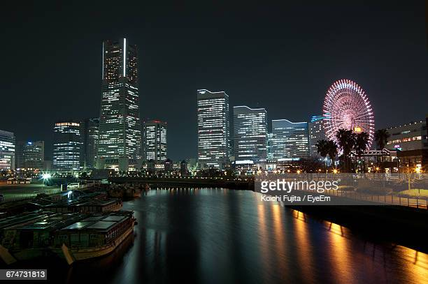 Illuminated Buildings And Ferris Wheel By River At Night