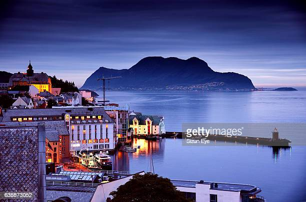 Illuminated buildings around the inner harbour of Alesund city in Norway at dusk.