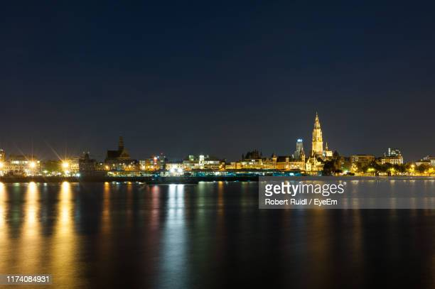 illuminated buildings at waterfront - antwerpen stad stockfoto's en -beelden