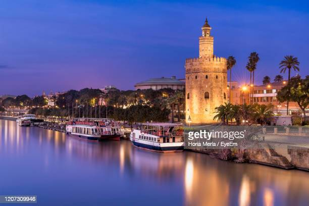 illuminated buildings by canal against sky at night - seville photos et images de collection