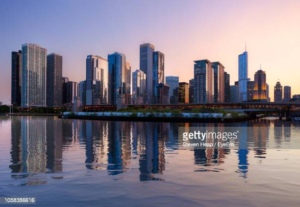 Illuminated Buildings By Lake In City Against Sky At Dusk