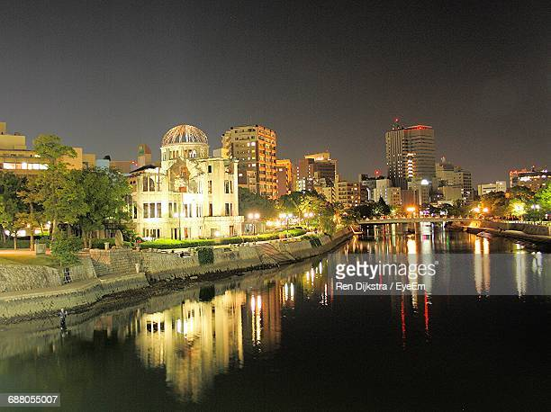 illuminated buildings by pond at peace memorial park - hiroshima peace memorial stock photos and pictures