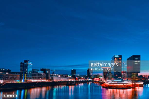 illuminated buildings by river against blue sky at night - north rhine westphalia stock pictures, royalty-free photos & images