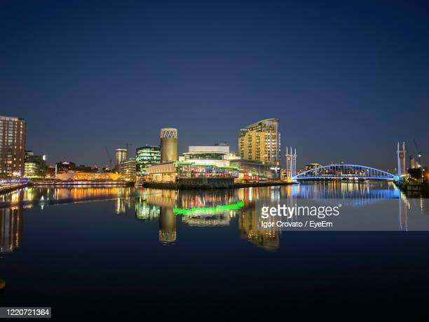 illuminated buildings by river against clear blue sky at night - manchester england stock pictures, royalty-free photos & images