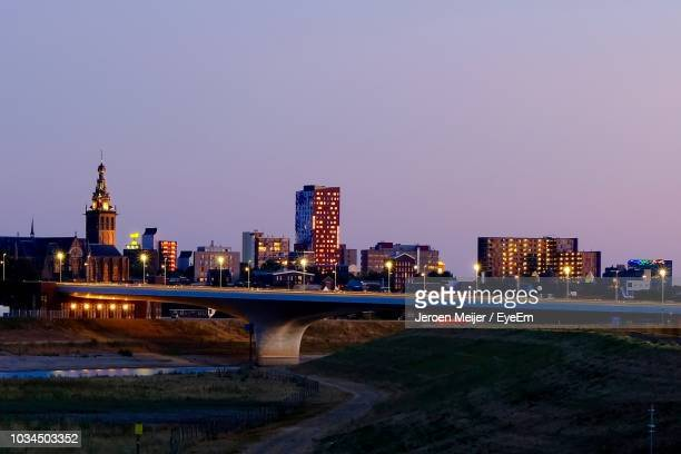 illuminated buildings by river against clear sky at night - nijmegen stock pictures, royalty-free photos & images