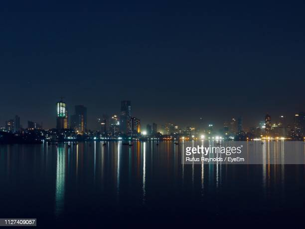 illuminated buildings by river against clear sky at night - india reynolds - fotografias e filmes do acervo