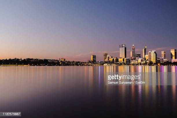 illuminated buildings by river against clear sky at sunset - perth australia stock pictures, royalty-free photos & images