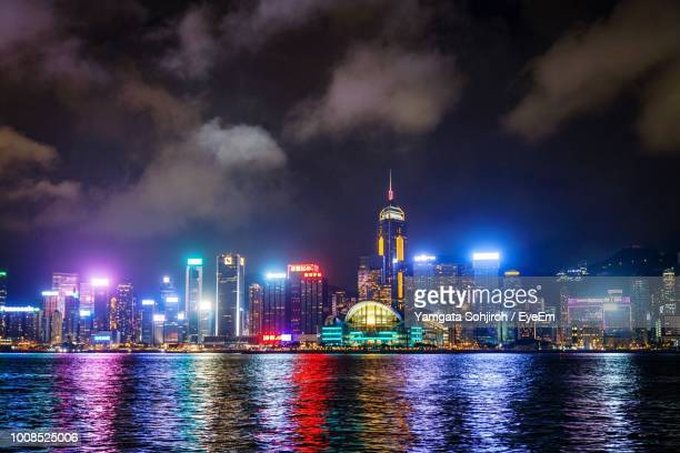 Illuminated Buildings By River Against Cloudy Sky