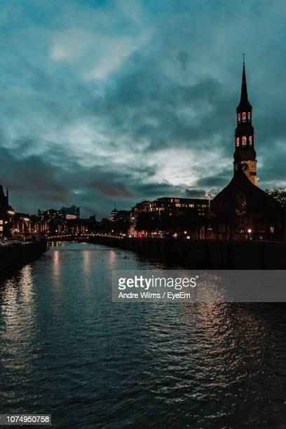 illuminated buildings by river against cloudy sky - andre wilms eyeem stock-fotos und bilder