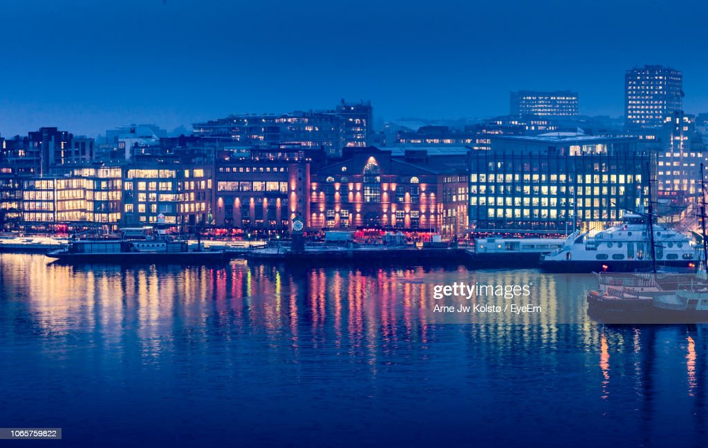Illuminated Buildings By River Against Sky At Dusk : Stock Photo