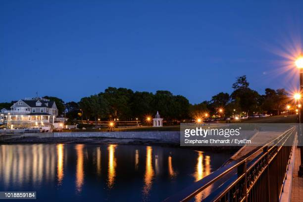 illuminated buildings by river against sky at night - bar harbor stock photos and pictures