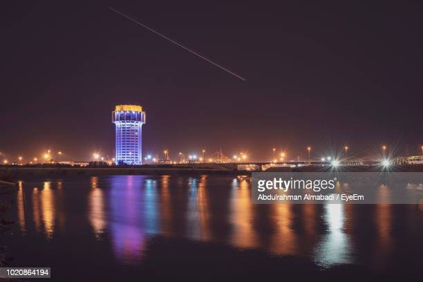 illuminated buildings by river against sky at night - jiddah stock pictures, royalty-free photos & images