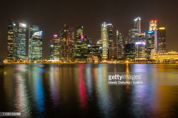 illuminated buildings by river against sky at night - marek stefunko imagens e fotografias de stock