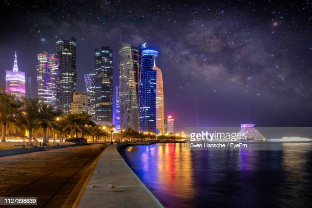 illuminated buildings by river against sky at night - doha photos et images de collection
