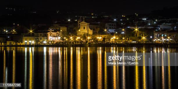 illuminated buildings by river against sky at night - メッシーナ ストックフォトと画像