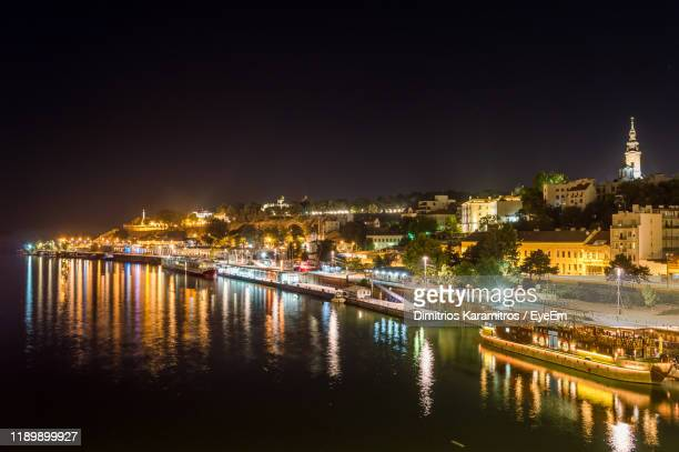 illuminated buildings by river against sky at night - belgrade serbia stock pictures, royalty-free photos & images