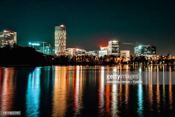 illuminated buildings by river against sky at night - bucarest foto e immagini stock