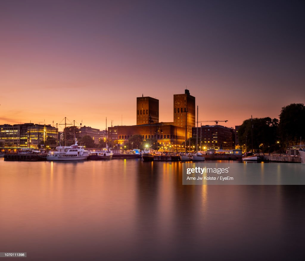 Illuminated Buildings By River Against Sky At Sunset : Foto de stock